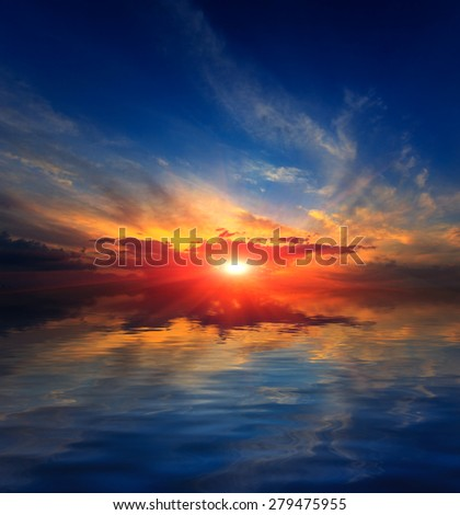 Nice sunset sky over water of lake - stock photo
