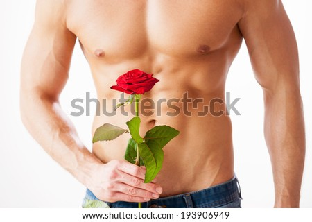 Nice surprise for her. Close-up of young muscular man with perfect torso holding single rose while standing against white background