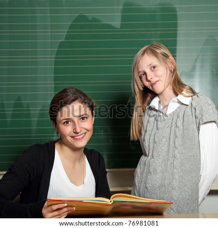 Nice teacher with a textbook and a student at the blackboard. They both smile at the camera - stock photo