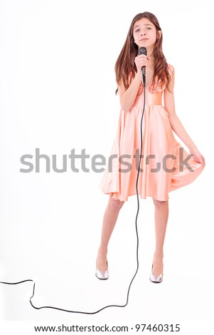 Nice teen girl singing with a microphone isolated