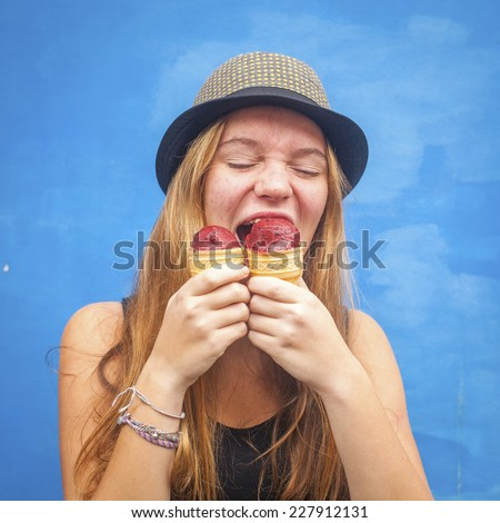 Nice teen girl with ice cream, blue wall background (Instagram style series) - stock photo