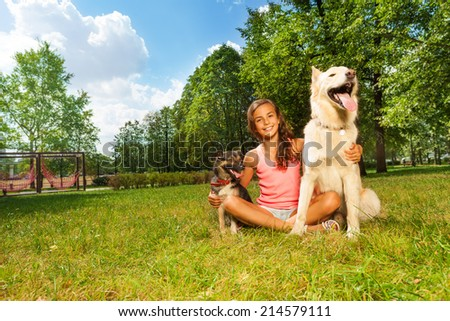 Nice teenage girl with her dogs in the park lawn - stock photo