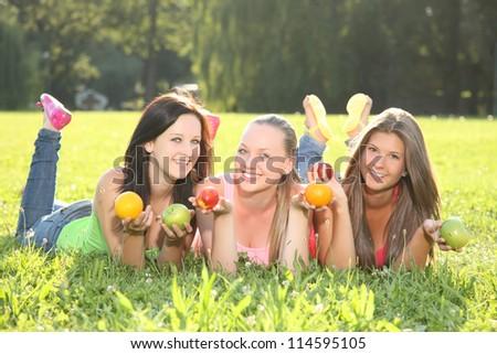 nice three girls posing with fruits - stock photo