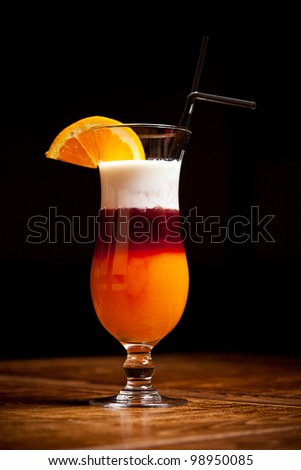 Nice three-layered cocktail on bar table whit orange decotation