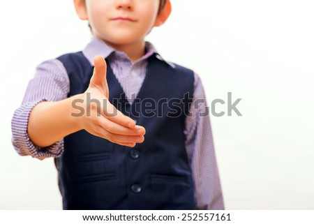Nice to meet you. Closeup portrait of cheerful little boy in formalwear stretching out hand for shaking while standing isolated on white background with selective focus - stock photo