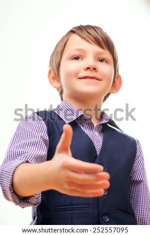 Nice to meet you. Low angle portrait of cheerful little boy in formalwear stretching out hand for shaking while standing isolated on white background with selective focus - stock photo
