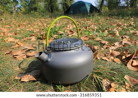 Nice tourist kettle on meadow in forest camp