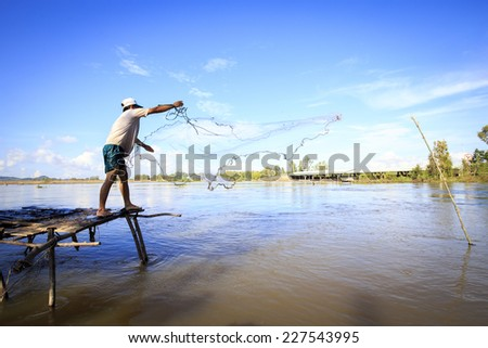 Nice, unique posture of fisherman when he cast a net from wooden boat on Vinh Te canal in An Giang, VietNam on Oct 28 2014 - stock photo