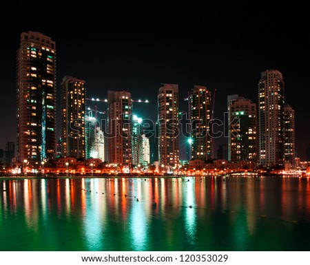 nice view of dubai city at night with reflections in water - stock photo