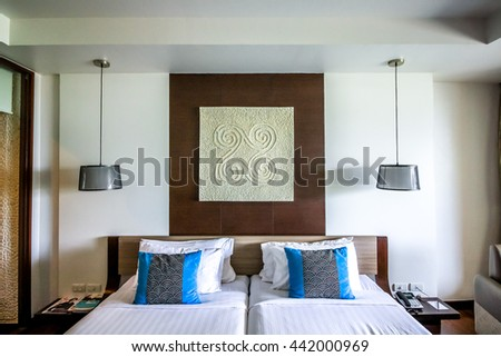 nice view of room double bed decorate with hanging lamp and blue pillows under warm light - stock photo