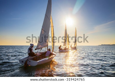 Nice view of the sailboats in the sunset leaving - stock photo