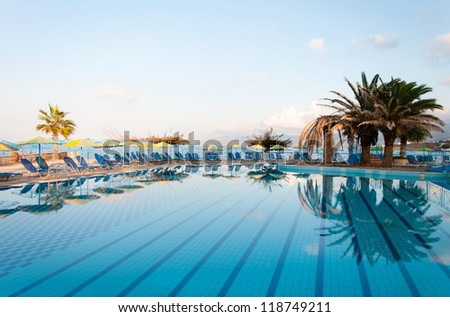 Nice view of the swimming pool with palm trees on the shore of the Mediterranean Sea in Greece. Crete. - stock photo