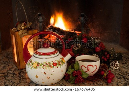Nice warm atmosphere in front of the fireplace during winter holidays. Teapot decorated with Christmas symbols and cup with tea.