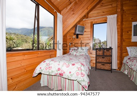 Nice warm interior of mountain wooden lodge bedroom. Fox Glacier Lodge, Fox Glacier, West Coast, South Island, New Zealand. - stock photo