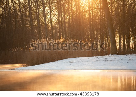 Nice warm tones over lake with snow at shore - stock photo