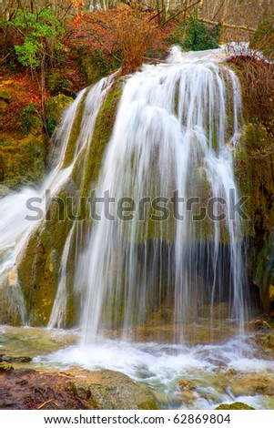 Nice waterfall in autumn forest - stock photo