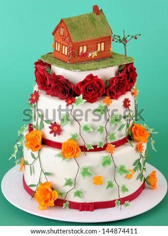Nice wedding cake with sugar flowers and little house on top - stock photo