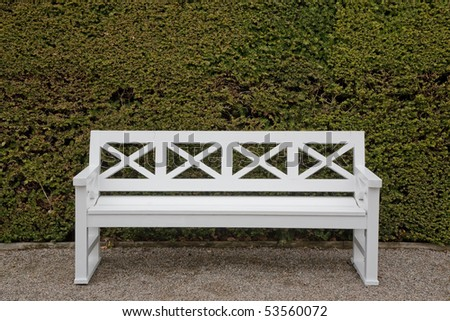 Nice white painted bench in park. Placed up against a huge newly cut hedge.