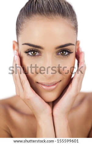 Nice woman holding her head and looking at camera on white background