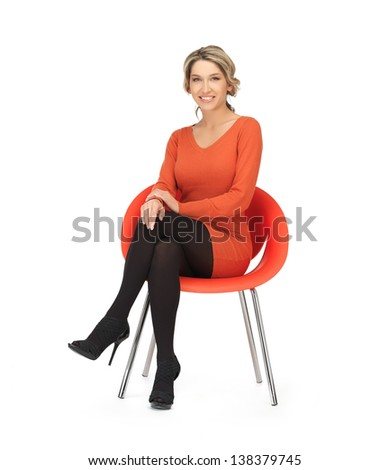 nice woman in dress sitting in chair - stock photo