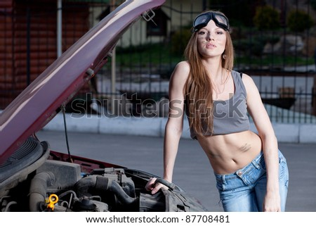 Nice woman mechanic repair broken red car - stock photo