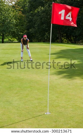 Nice woman surveying her putt on the fourteenth hole.  She is looking at the ball while holding her legs, wearing a cap and a sportswear outfit - stock photo
