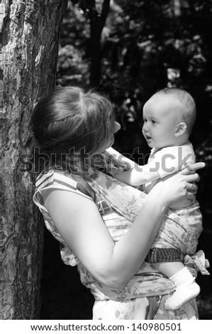 Nice woman with her baby boy in a sling baby carrier