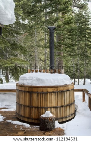 Nice wooden hot tub covered with snow, winter background, northern california - stock photo