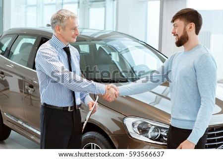 Happy Young Man Shaking Hands With Professional Mature Car Dealer After