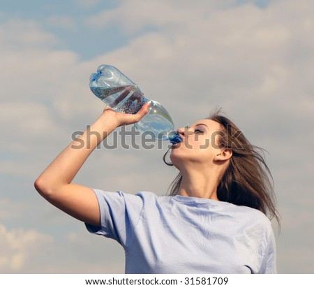 nice young beautiful woman drinks water and  plastic bottle