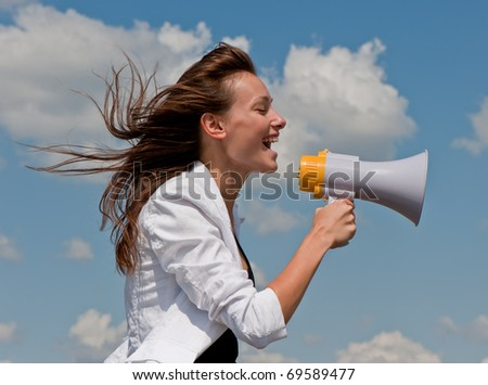 nice young businessman shouts in a megaphone against the blue sky with clouds - stock photo
