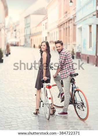 nice young couple , bike stops to turn heads and give a toothy smile toward the camera in a European city in a summer sunny day - stock photo