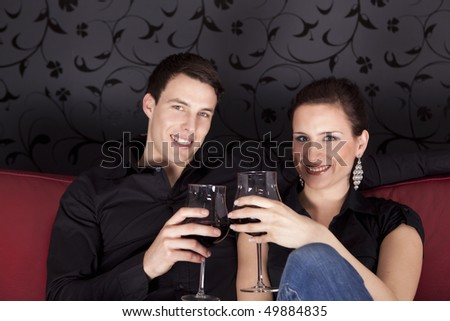 Nice young couple drinking red vine and smiling at the camera.