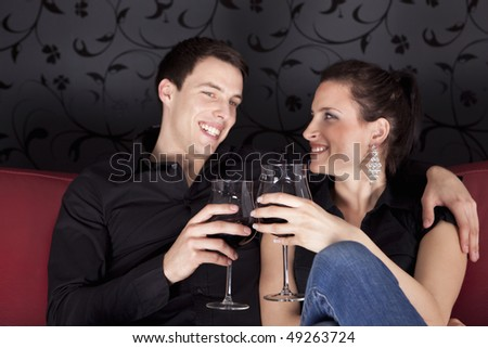 Nice young couple relaxing on the red sofa with glass of red vine