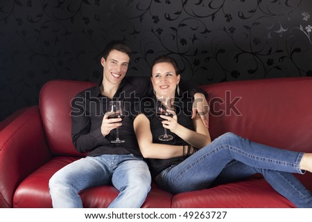 Nice young couple relaxing on the red sofa with glass of vine