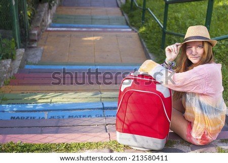 Nice young girl sitting on the steps with a red suitcase, travel concept. - stock photo