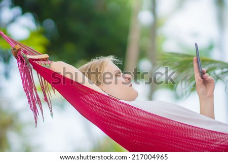 Nice young lady listen music and read book on e-ink reader in  hummock under palm trees on tropical beach. Close up - stock photo