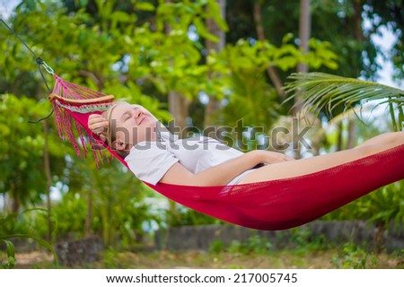 Nice young lady listen music in hummock under palm trees on tropical beach - stock photo