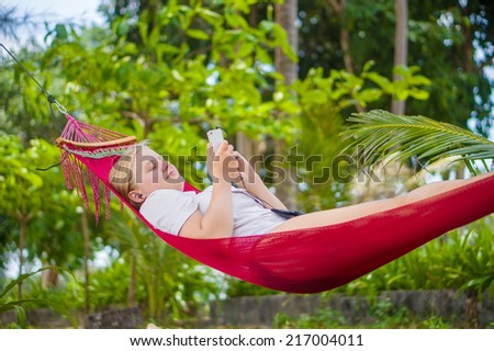 Nice young lady listen music use modern smart phone in hummock under palm trees on tropical beach - stock photo
