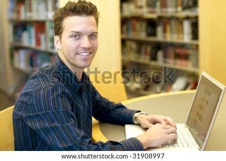 Nice young man researching information on a laptop