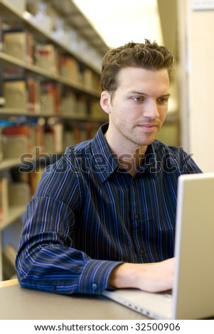 Nice young man researching information on a laptop - stock photo