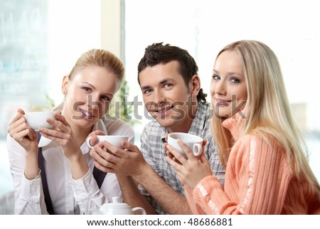 Nice young people drink coffee on a forward background - stock photo