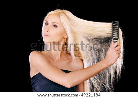 Nice young woman combs hair, it is isolated on black background.