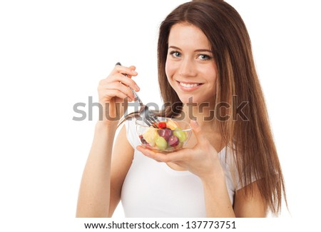 Nice young woman eating fruits and smiling, isolated on white