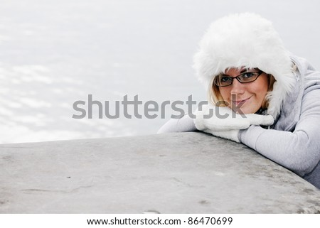 Nice young woman in warm winter outfit and a warm wool cap. - stock photo