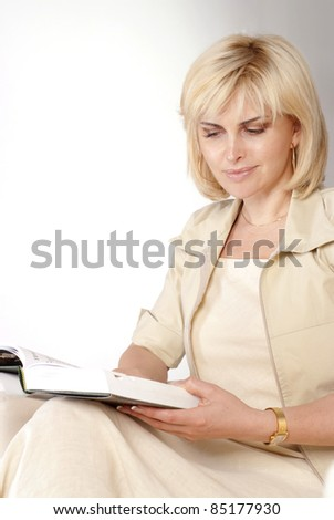 nice young woman reading a book on sofa