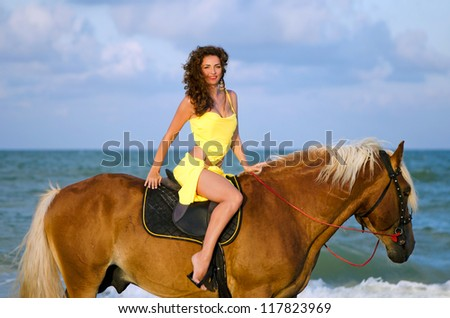 Nice young woman riding a horse on the beach - stock photo