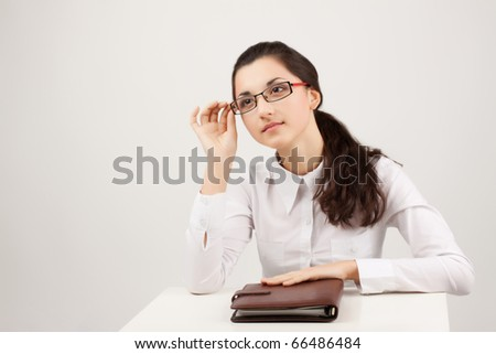nice young woman with with the daily log behind a table on a light background