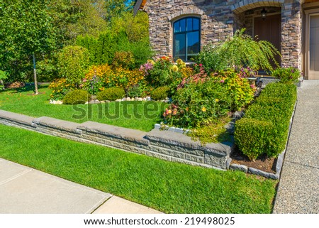 Nicely decorated colorful flowerbed and trimmed bushes at front yard lawn in front of the house. Landscape design.