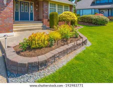 Nicely decorated colorful flowerbed, front yard, lawn with stones and bushes as a decorative elements. Landscape design. - stock photo